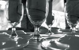 Served table with glasses. Clean diningware on table black and white photo. Empty wine glass and plate vintage banner. Hospitality of restaurant or cafe Stock Photos