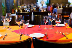 Served table with red and orange tablecloth, wine glasses, white plates and cutlery. (Soft focus.). Restaurant hall. Table with red and orange tablecloth, wine stock images