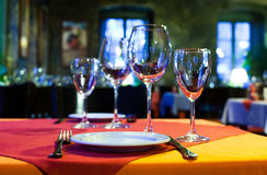 Served table with red and orange tablecloth, wine glasses, white plates and cutlery. (Soft focus.) Stock Image