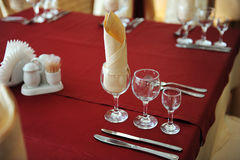 Served table in a restaurant. Cream and maroon colors. Bows drapery on chairs. Close up Stock Image