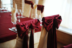 Served table in a restaurant. Cream and maroon colors. Bows drapery on chairs. Close up Royalty Free Stock Photo