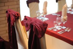 Served table in a restaurant. Cream and maroon colors. Bows drapery on chairs. Close up Stock Photos