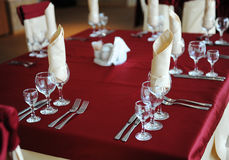 Served table in a restaurant. Cream and maroon colors. Bows drapery on chairs. Close up Stock Photography