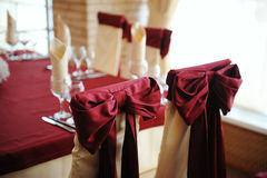 Served table in a restaurant. Cream and maroon colors. Bows drapery on chairs. Close up Royalty Free Stock Photos