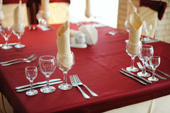 Served table in a restaurant. Cream and maroon colors. Bows drapery on chairs. Close up Stock Images