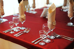 Served table in a restaurant. Cream and maroon colors. Bows drapery on chairs. Close up Royalty Free Stock Images