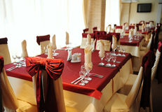 Served table in a restaurant. Cream and maroon colors. Bows drapery on chairs Royalty Free Stock Photo