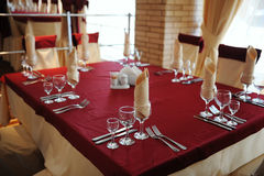 Served table in a restaurant. Cream and maroon colors. Bows drapery on chairs. Modern interior Stock Images