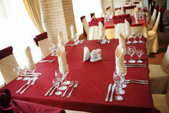 Served table in a restaurant. Cream and maroon colors. Bows drapery on chairs. Modern interior Stock Image