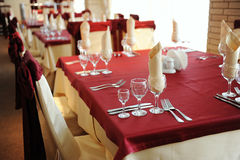 Served table in a restaurant. Cream and maroon colors. Bows drapery on chairs Royalty Free Stock Photography