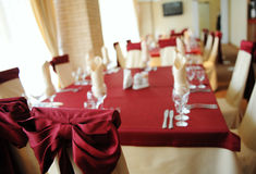 Served table in a restaurant. Cream and maroon colors. Bows drapery on chairs Royalty Free Stock Photos
