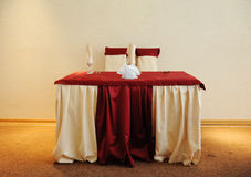 Served table in a restaurant. Cream and maroon colors. Bows drapery on chairs. Modern interior Stock Photography