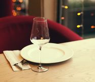 Served table in the restaurant. Empty wine glasses, a plate on t. He background of the bright lights of the Christmas garland stock images