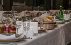 Served table in restaurant, glasses, dishes with cheese and bread stock photography