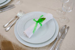 Served table in restaurant. Napkin with green tape on white plate with cutlery Royalty Free Stock Images