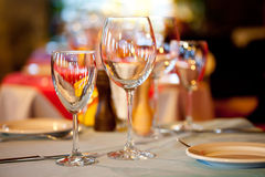 Served table in a restaurant. Romantic holiday Interior with wine glasses and crockery Stock Photos