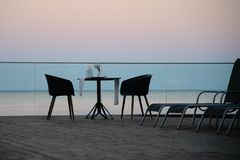 Served table in the restaurant on the sea sunset background royalty free stock photo