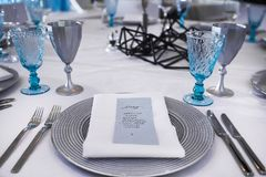 Served table in the restaurant - silver and blue wine glasses, plate, forks, knives and napkin with menu stock photography