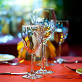 Served table in a restaurant with tablecloth, napkin, wine glass, cutlery. Royalty Free Stock Photography