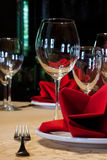 Served table in a restaurant with a tablecloth, red napkins, wine glasses and cutlery. Stock Photo