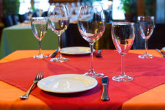 Served table in restaurant. white plate knife fork and wine glasses on red napkin. romantic interior concept Stock Photography