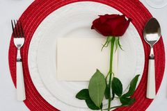 Valentines Day Dinner. Served table for Valentines Dinner with fresh rose flowers and copy space on blank paper Royalty Free Stock Photos