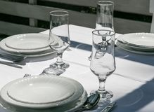 Served table with white tablecloth, plates, wine glasses prepared for event. stock image