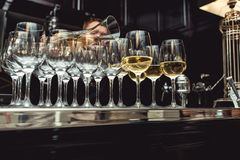 Bartender pouring white wine into glass at wine tasting. Served table at wine tasting. bartender pouring white wine from a decanter into glasses Stock Image