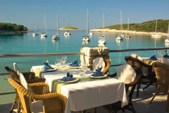 Served tables in beach restaurant. Near lagoon with yachts Stock Images