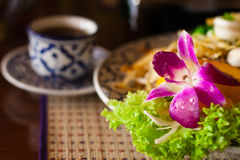 Served thai noodles and a cup of tea. Beautifully served thai noodles with an orchid and a cup of tea, shallow DOF, focus on the flower Stock Photos