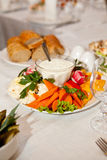 Served vegetable plate with sauce and bread on fest table. Served vegetable plate from carrots, paprika, salads with sauce and bread on fest table near glasses Stock Photo