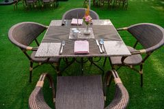 Served wicker table with chairs outside. Table with wicker chairs served for meal on green lawn of resort royalty free stock photo