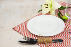 Served wooden restaurant table with settings on red checkered tablecloth Stock Photo