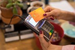 Serveerster die betaling van creditcard wirelessly op POS-terminal nemen stock foto's