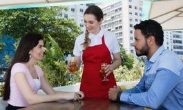 Serveerster die koud bier dienen aan een plaats van het liefdepaar bij restaurant Stock Foto