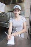 Serveerster die orde in een snel voedselrestaurant neemt Stock Foto