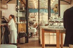 Serveerster en klanten van modern stijlrestaurant die diner in helder binnenland hebben Royalty-vrije Stock Afbeeldingen