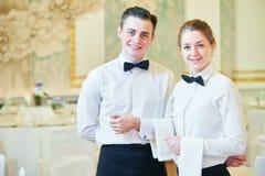 Serveerstervrouw en kelnersman in restaurant Stock Foto's