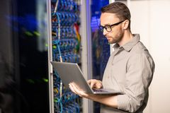 Server engineer troubleshooting problem. Serious thoughtful handsome young server engineer in glasses standing in database center and using laptop while stock photography