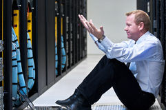 Server failure. Business man sitting in a data center looking frustrated with the current system. He is looking for a better IT solution Royalty Free Stock Photos