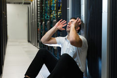 Server frustration. Business man sitting in a data center looking frustrated with the current system. He is looking for a better IT solution Royalty Free Stock Photography