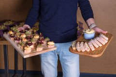 Server holding wooden trays of appetizers in each Royalty Free Stock Photo