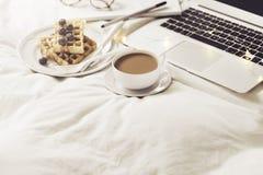 Server mit Frühstück und Laptop auf Bett Stockfotos