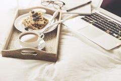 Server mit Frühstück und Laptop auf Bett Stockbild