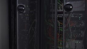 Server rack flashing led lights are in a modern data center. Are located behind an iron door with round openings stock video footage