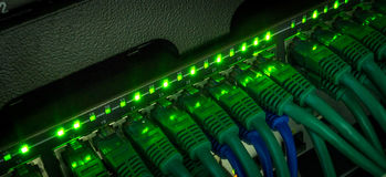 Server rack with green internet patch cord cables. Connected to black patch panel in server room horizontal. Glowing in dark stock photo