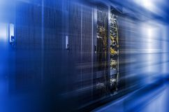 Server racks row in big data center with depth of field in cool blue tone and motion effect. Server racks row in big data center with depth of field in cool blue royalty free stock photo