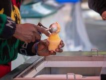 Server scoops orange flavored Italian ice royalty free stock image