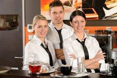 Server som tre poserar i likformig i kafé Arkivfoto