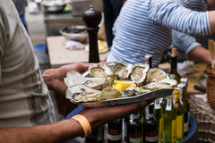 Server with Tray of Fresh Oysters and Lemon Wedges Royalty Free Stock Images